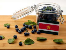 Suriname flag on a wooden plank with blueberries  on whi Stock Images