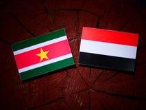 Suriname flag with Yemeni flag on a tree stump isolated Royalty Free Stock Images