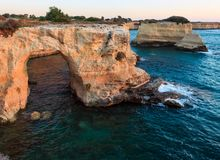 Surise Faraglioni at Torre Sant Andrea, Italy. Sunrise seascape with cliffs, rocky arch and stacks faraglioni, at Torre Sant Andrea, Salento sea coast, Puglia Royalty Free Stock Images