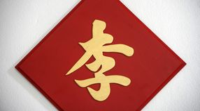 The surname sign on the white wall, The golden Chinese word handwriting style on the red wooden sign. Chinese word : Lee, It is a surname royalty free stock image