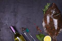 Surowa świeża ryba, białego wina butelka, cytryna i ziele na szarość, drylujemy tekstury tło Widok od above, odgórny studio strza Obrazy Stock