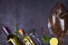 Surowa świeża ryba, białego wina butelka, cytryna i ziele na szarość, drylujemy tekstury tło Widok od above, odgórny studio strza Zdjęcia Stock