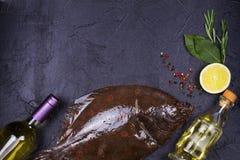 Surowa świeża ryba, białego wina butelka, cytryna i ziele na szarość, drylujemy tekstury tło Widok od above, odgórny studio strza Zdjęcie Stock