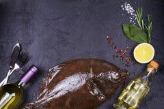 Surowa świeża ryba, białego wina butelka, cytryna i ziele na szarość, drylujemy tekstury tło Widok od above, odgórny studio strza Obraz Stock