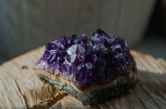 Surowa ametyst skała z odbiciem na naturalnym drewnianym krystalicznym ametist obrazy royalty free