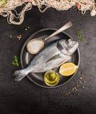 Surowa dorado ryba w szarym wieśniaka talerzu z cytryną, olej i łyżka sól na zmroku, drylujemy tło Zdjęcie Stock