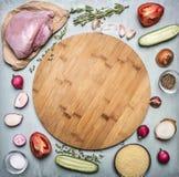 Surowa indycza pierś z ogórkami nad drewnianą tnącą deską na nieociosanego drewnianego tła odgórnym widoku i ziele pomidoru i pie Zdjęcie Stock