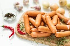 Surowa kiełbasa dla smażyć na tnącej desce z rozmarynami i pikantność na białym drewnianym nieociosanym tle zdjęcia stock