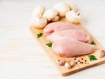 Surowa kurczak pierś polędwicowa z pikantność na drewnianej desce na białym drewnianym stole, boczny widok, kopii przestrzeń obraz stock