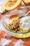 Surowa myjąca jagła, ryż i rodzynki w szklanej niecce w trakcie kucharstwa, doimy dyniową owsiankę obrazy stock