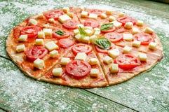 Surowa pizza z mąką na zielonym drewno stole Zdjęcia Royalty Free