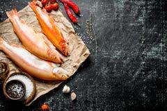 Surowa pstrąg ryba na papierze z pomidorami, chili pieprzem i pikantność, obrazy stock