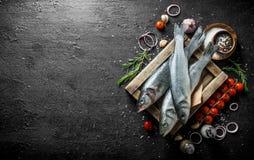 Surowa ryba na drewnianej tacy z pomidorami, pikantność, czosnkiem, rozmarynami i cebulkowymi pierścionkami, fotografia royalty free
