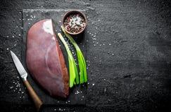 Surowa wątróbka na kamiennej desce z zielonymi cebulami i pikantność fotografia royalty free