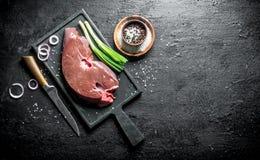 Surowa wątróbka na tnącej desce z nożem, pikantność i cebulami, obrazy stock