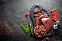 Surowa wątróbka z czereśniowymi pomidorami, pikantność i koperem na tnącej desce, obraz stock