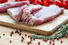 Surowa wieprzowina na tnącej desce i warzywach Obraz Royalty Free