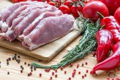 Surowa wieprzowina na tnącej desce i warzywach Fotografia Stock