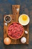 Surowa zmielona wołowina w pucharze na tnącej desce z pikantność na ciemnym nieociosanym tle Składniki dla kulinarnych cutlets, k obraz royalty free