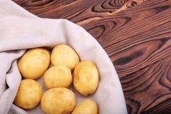 Surowe, świeże, ciężkie jasnobrązowe nowe grule na szarej torbie na brown drewnianym stole i, Healthful i świezi warzywa Zdjęcie Stock