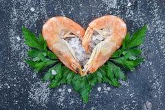 Surowe krewetki, garnele z sercami z condiments na kamiennym tle, posypującym z morze solą i ziele Garneli kłamstwo w formie Fotografia Stock