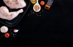 Surowe kurczak nogi z ziele czosnek i pomidory przygotowywający gotować na czarnym kamiennym tle, odgórny widok Zdjęcie Stock