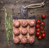 Surowe mięsne piłki z warzywami, masłem i ziele na drewnianym nieociosanym tło odgórnego widoku zakończeniu up, Zdjęcia Royalty Free