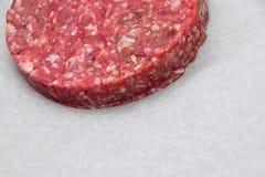 Surowego mięsa hamburger, hamburger na białym pergaminie zdjęcia royalty free