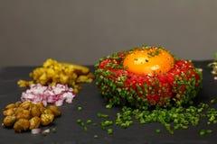 Surowego mięsa tartare stek i jajeczny yolk na czerni wsiadamy fotografia stock