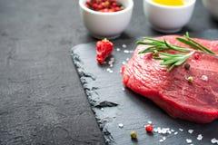 Surowego mięsa wołowiny stki na czerń łupku wsiadają zbliżenie, kopii przestrzeń Zdjęcie Royalty Free