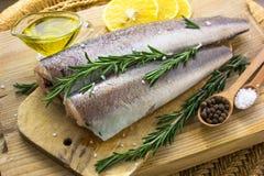 Surowej ryba morszczuk z pikantność i morze solą oliwi na desce zdjęcie royalty free