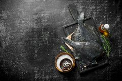 Surowej ryby flądra na tnącej desce z rozmarynami i pikantność zdjęcia stock