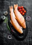 Surowej ryby pstrąg na tnącej desce z pomidorami, pikantność i pokrojonymi cebulami, zdjęcie stock