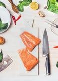 Surowi łososiowi stki na białej tnącej desce z nożem na kuchennego stołu tle z składnikami, odgórny widok Zdrowy łasowanie i gruc Zdjęcia Royalty Free