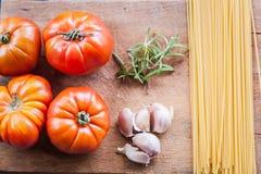 Surowi świezi pomidory z spaghetti, czosnkiem i ziele, obrazy stock