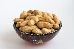 Surowi arachidy w skorupie na glinianej filiżance na białym tle fotografia stock