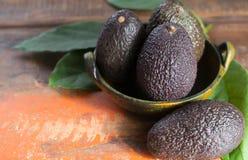 Surowi dojrzali ciemnozieleni avocados z liśćmi na drewnianym tle Obrazy Stock