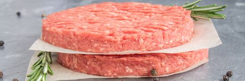 Surowi hamburgery na pergaminowym papierze z rozmarynami Siwieje marmurowego backgr zdjęcia royalty free