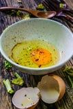 Surowi jajka w pucharze na drewnianym stole Fotografia Stock