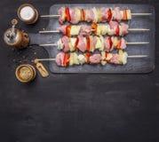 Surowi kebabs z wieprzowiną, warzywami i owoc na rocznik tnącej desce z pikantności tła odgórnego widoku drewnianym nieociosanym  Zdjęcia Stock