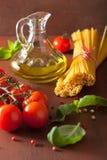 Surowi makaronu oliwa z oliwek pomidory włoski kucharstwo w nieociosanej kuchni Obrazy Stock