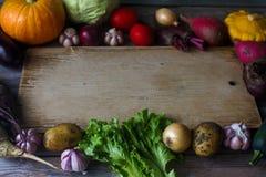 Surowi organicznie świezi warzywa i drewniana deska w wieśniaku projektują Żniwo czas, kolorowi warzywa, zdrowy styl życia Obraz Royalty Free