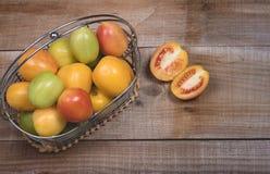 Surowi pomidory na drewnianym tle Zdjęcie Stock