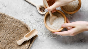 Surowi ryż groszkują w drewnianych kubkach na stole zdjęcie wideo