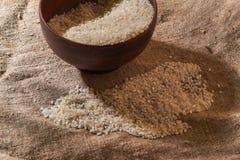 Surowi ryż w pucharze na parciaku Uncooked jedzenie Selekcyjna ostrość obraz stock