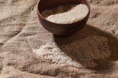 Surowi ryż w pucharze na parciaku Uncooked jedzenie Selekcyjna ostrość zdjęcie stock