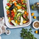 Surowi składniki dla lunchu - świezi siekający warzywa w niecce na błękitnym tle, odgórny widok obrazy stock