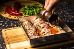 Surowi wieprzowina klopsiki w kruszcowym pieczenia naczyniu w pomidorowym kumberlandzie zdjęcie royalty free