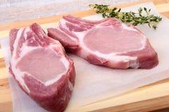 Surowi wieprzowina kotleciki, pikantność i rozmaryny na tnącej desce, Przygotowywający dla gotować obrazy royalty free