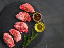 Surowi wieprzowina policzki mięśni na zmroku szary tło, odgórny widok z rozmarynami i pikantność -, obrazy stock